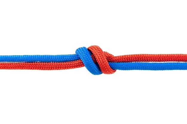 2本の赤と青のコードが接続されています。白い背景で隔離のコードの結び目。