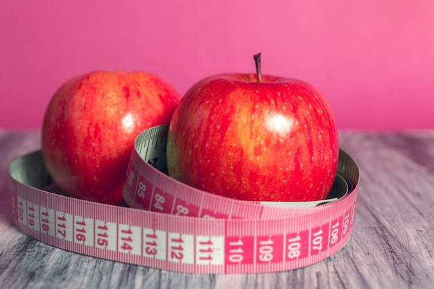 Two red apple with measuring tape on pink. healthy diet concept.