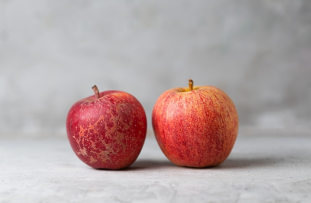 Two red apples on a green vertical