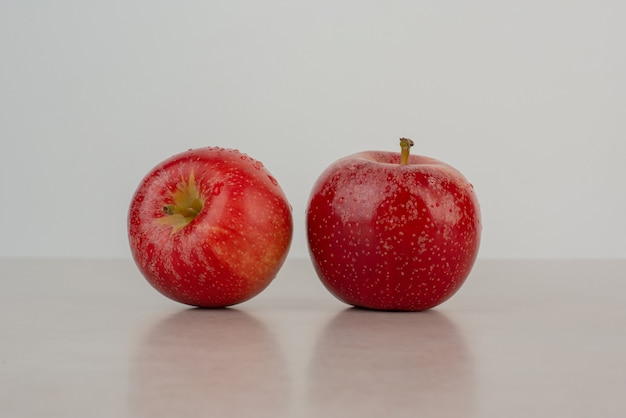 Two red apples on marble table .