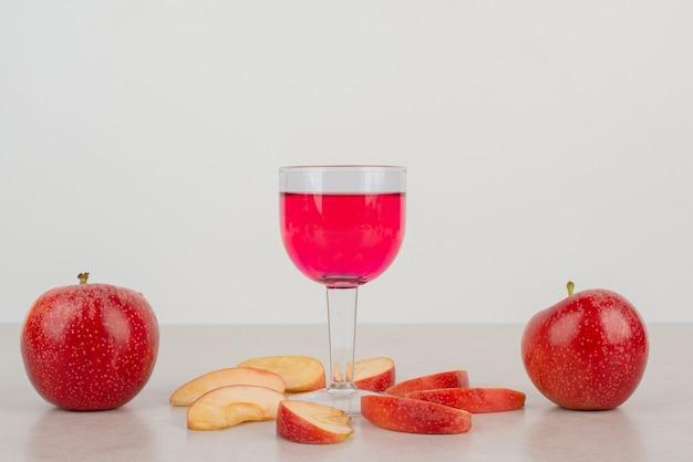 Due mele rosse, fette di mela e un bicchiere di limonata.