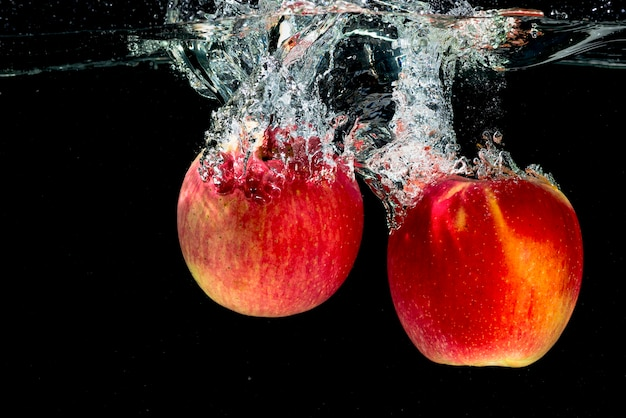 Two red apples splashing in the water