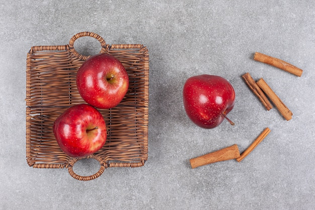Two red apples in wooden basket with cinnamon sticks