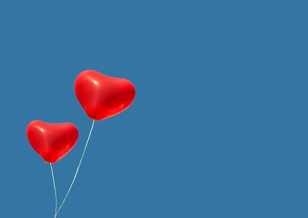 헬륨으로 가득 찬 두 개의 빨간 풍선이 발렌타인 데이를 위해 푸른 하늘에 날아갑니다.