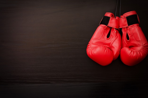 Two red boxing gloves hanging on a black table