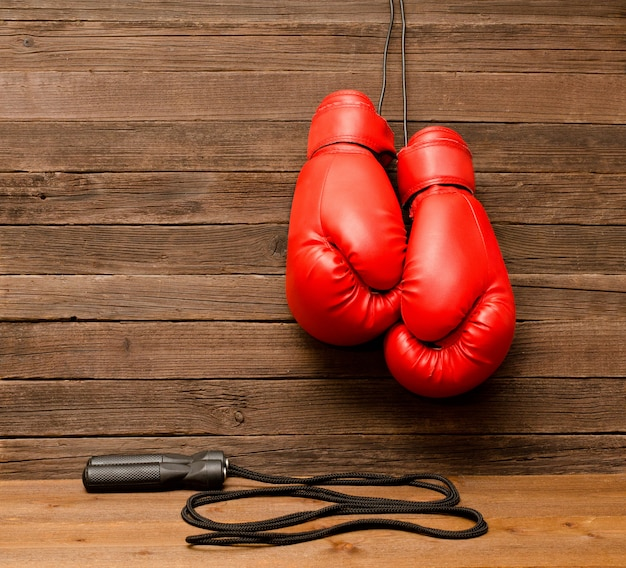 Two red boxing gloves hung on a wooden brown background