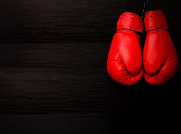 Две красные боксерские перчатки в верхнем углу рамки на черном фоне, пустое пространство