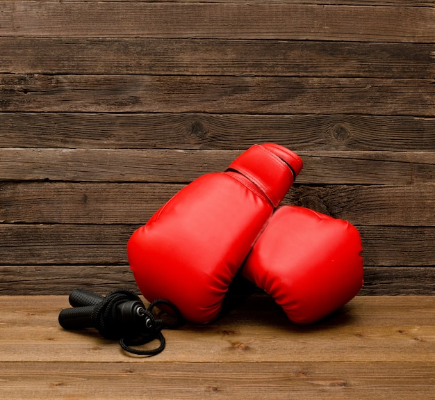 Two red boxing gloves lie on a wooden brown wall, skipping rope empty space