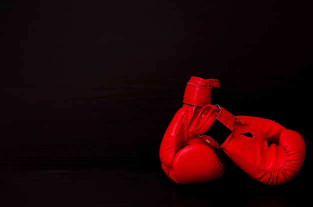 Two red boxing gloves on the side of the frame on a black background, empty space