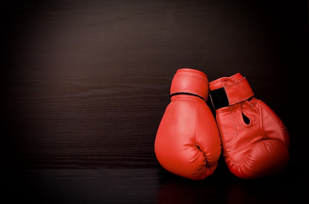Two red boxing gloves on the side of the frame on a black background
