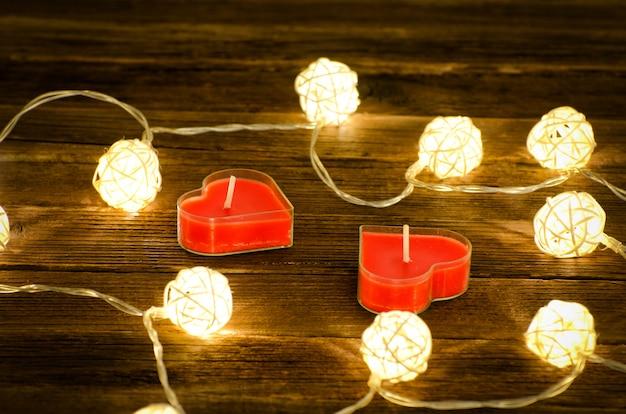 ハートの形をした2つの赤いろうそくと木製の空間に籐製の輝くランタン。閉じる