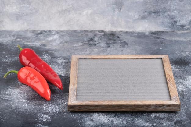 Два красных перца чили и пустая рамка на мраморной поверхности.