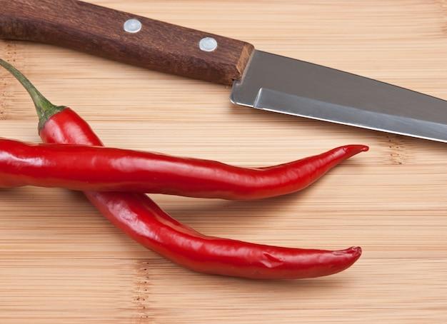 2つの赤唐辛子とキッチンテーブルの上のナイフ