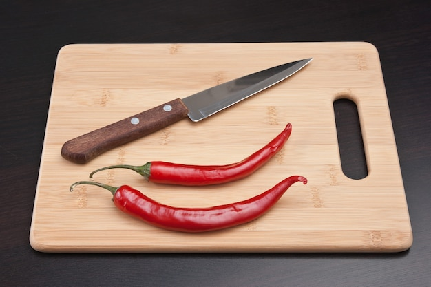 Two red chili peppers and knife on the kitchen table