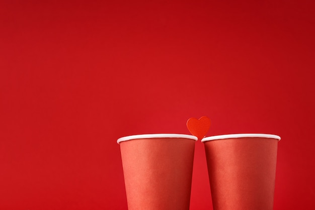 Two red coffee cups with  heart as couple in love on red surface. valentines day and romantic concept