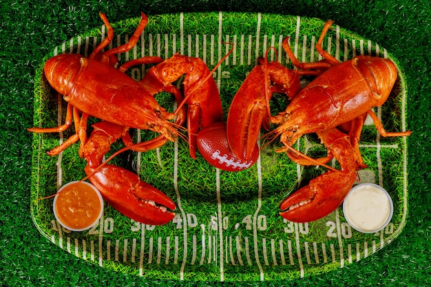 Two red cooced lobsters on green plate with football ball. american football concept.