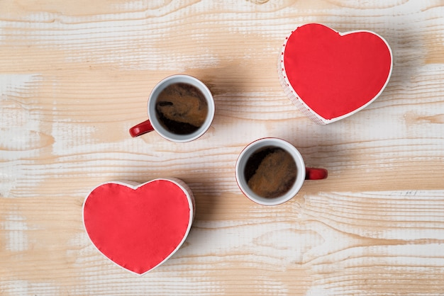 Two red cups of coffee and heart shaped boxes. date, valentine's day. top view
