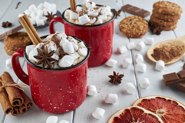 Two red cups of hot chocolate with marshmallow, anise and cinnamon sprinkled with cocoa powder