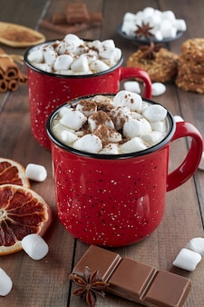 Two red cups of hot chocolate with marshmallow sprinkled with cocoa powder on a wooden table