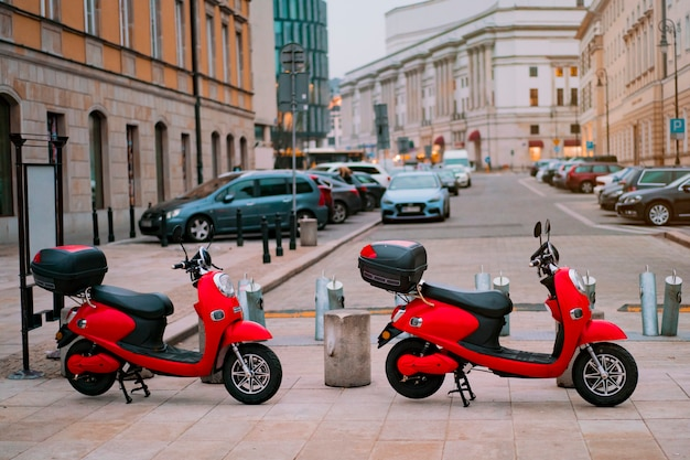 Two red electric motorbikes for rental parked on the street