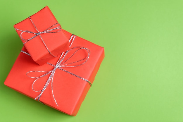 Two red festive presents on green pastel background.