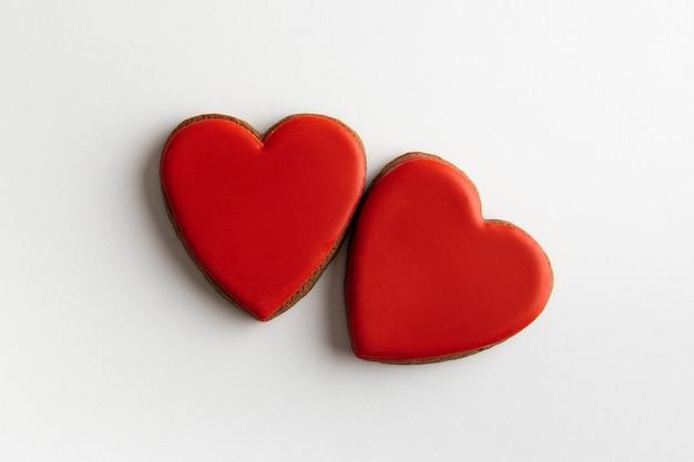 白い背景、上面図に2つの赤いジンジャーブレッドの心。バレンタイン・デー。