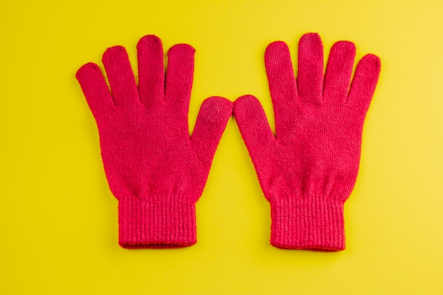 Two red gloves isolated on yellow