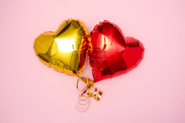 Two red and golden hearts foil balloons upper view on pink valentines day background