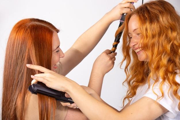 두 명의 빨간 머리 미녀, 하나는 머리카락을 곧게 펴고 다른 하나는 곱슬 머리를 만듭니다. 헤어 스타일 만들기. 이발.
