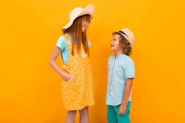 Two red-haired boy and girl in summer hats talking to each other on a yellow