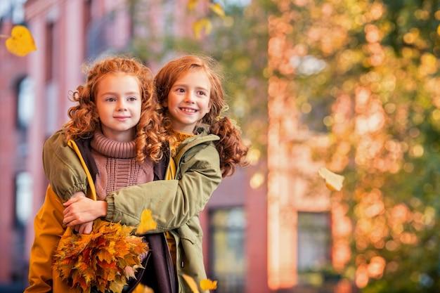 黄金色の紅葉の秋に、2人の赤毛の女の子、姉妹が街の通りを元気に歩きます。