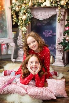 Две рыжие сестры возле новогодней елки.