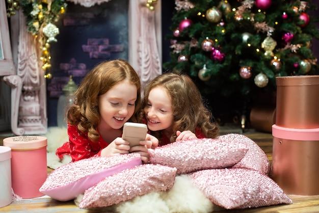 電話を見ている新年の木の近くの2人の赤毛の姉妹。クリスマス休暇の雰囲気、照明、ギフト、スタイル、ガジェット、スマートフォン。オンラインコミュニケーション、インターネット