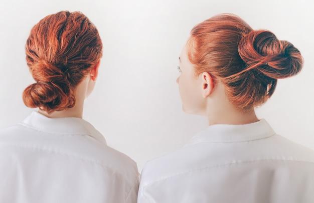 2つの赤い髪の姉妹はシャツの白い背景で隔離のスタンドします。女性は背を向ける。 Premium写真