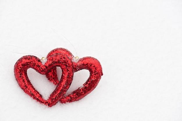 Две красные сердечные фигуры на фоне снега