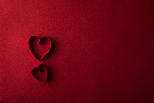 Two red hearts against red background