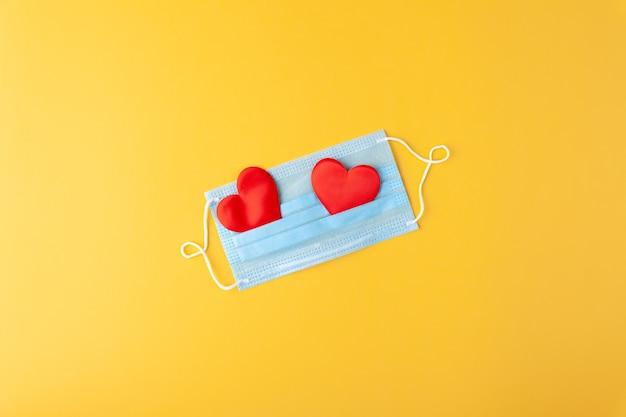 2つの赤いハートと抗流行性の青い医療マスク、使い捨て医療用品、コンセプトバレンタインデー、愛、医師のおかげで、コピースペース、水平、黄色の壁