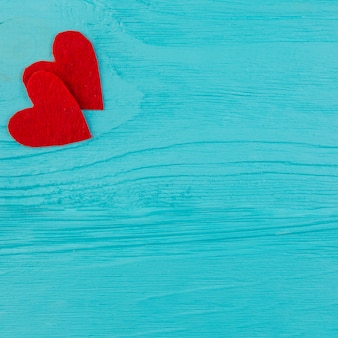 Two red hearts on blue wooden surface