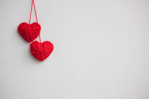 Two red hearts from woolen threads on a light background. valentine's day concept.