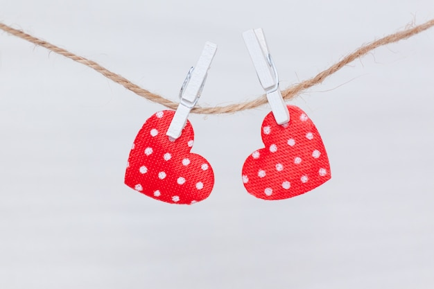 Two red hearts hanging on a thread on white wooden background. valentine's day, love, wedding concept. flat lay, top view.