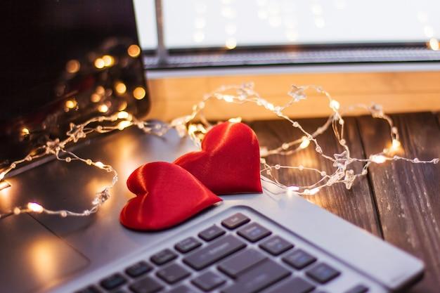 Два красных сердца лежат на деревянном столе возле ноутбука, свадебная любовь на день святого валентина