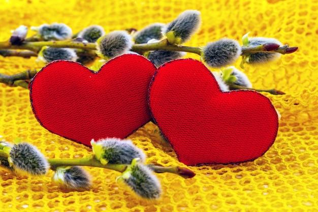 イヤリングと柳の枝の近くの2つの赤いハート、バレンタインデーおめでとうございます