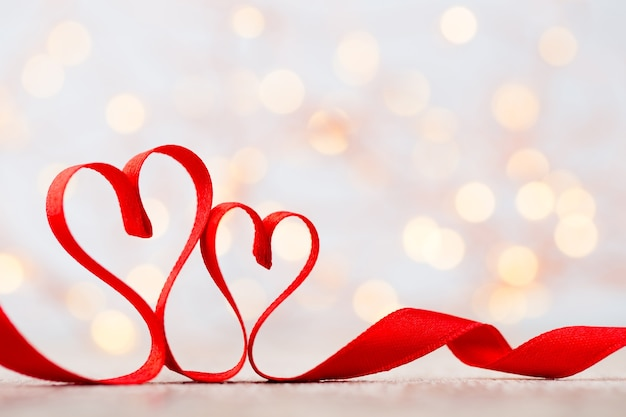 リボンの2つの赤いハート。バレンタインデーのグリーティングカード。