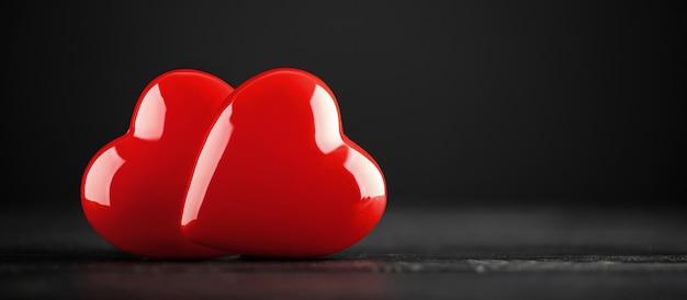 暗い木製のテーブルの上の2つの赤いハート。バレンタインデーのグリーティングカード