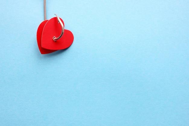 Два красных сердца на металлическом крючке на синем фоне