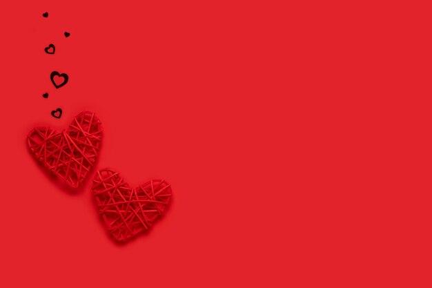 Два красных сердца на красном фоне. концепция дня святого валентина. копия пространства. вид сверху.