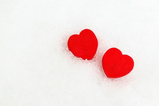 コピースペースと白い雪の背景に2つの赤いハート。バレンタインデーのシンプルなカード