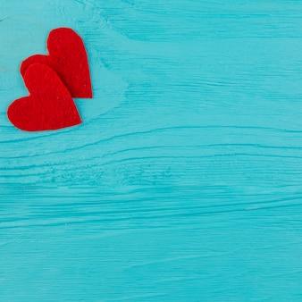 青い木製の表面に2つの赤い心