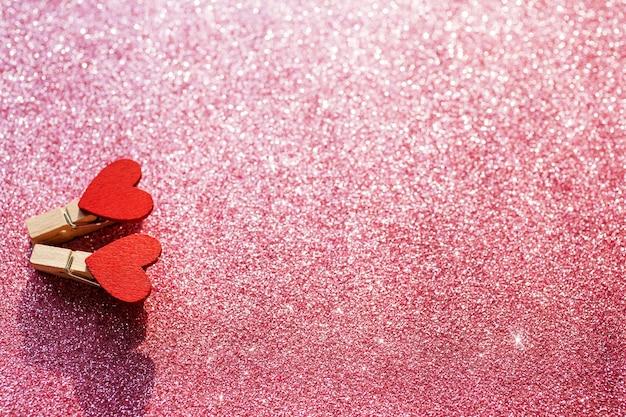 흐릿한 핑크 반짝이 배경에 두 개의 빨간색 하트. 발렌타인 데이 개념. 선택적 초점. 공간을 복사하십시오.