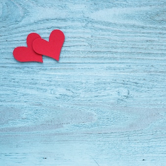 Two red hearts on wooden table